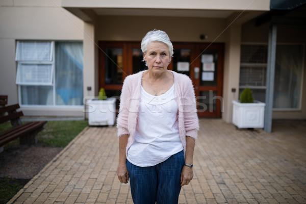 Portrait of serious senior woman standing on entrance Stock photo © wavebreak_media