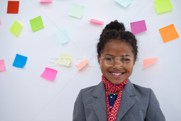 Portrait of smiling businesswoman standing  against sticky notes on wall Stock photo © wavebreak_media