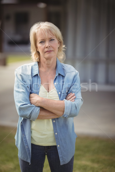 Senior woman standing with arms crossed outside her house Stock photo © wavebreak_media