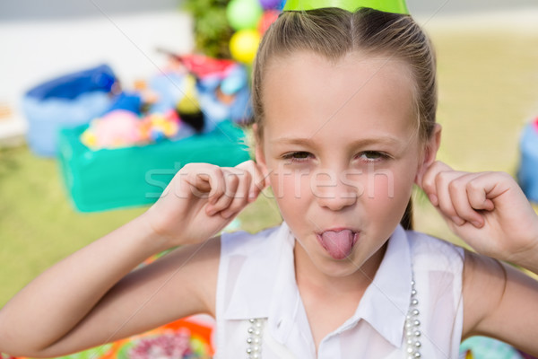 Stock photo: Close up portrait of girl holding ears while sticking out tongue