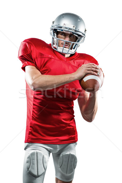 Confident American football player in red jersey holding ball Stock photo © wavebreak_media