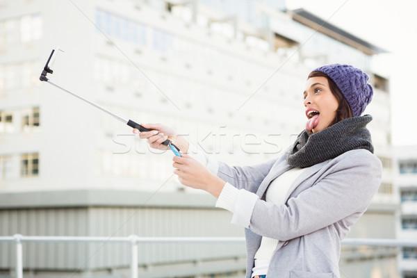 Happy woman using selfie stick Stock photo © wavebreak_media