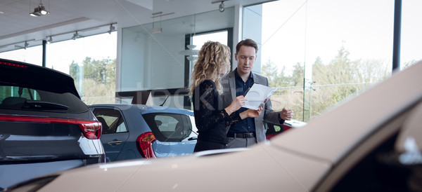 Stock photo: Female customer showing brochure to salesman in showroom