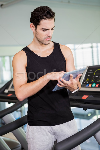 Serious man on treadmill standing with tablet Stock photo © wavebreak_media