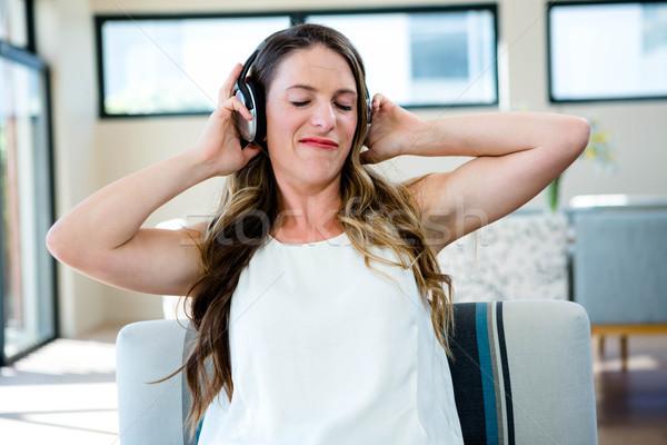 woman grimacing listening to headphone Stock photo © wavebreak_media