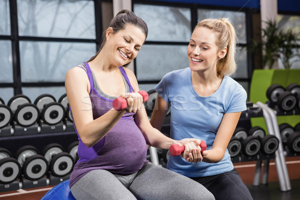 Trainer helping pregnant woman at the gym Stock photo © wavebreak_media