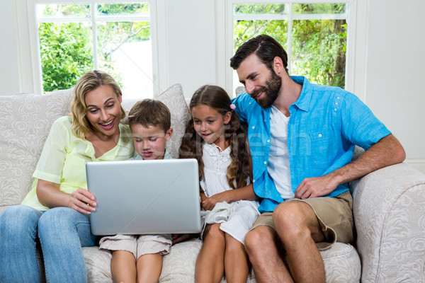 Smiling children with parents using laptop at home Stock photo © wavebreak_media