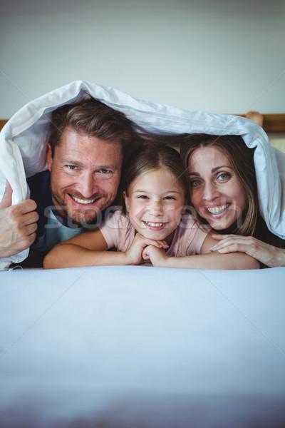Happy family lying under a blanket on bed Stock photo © wavebreak_media
