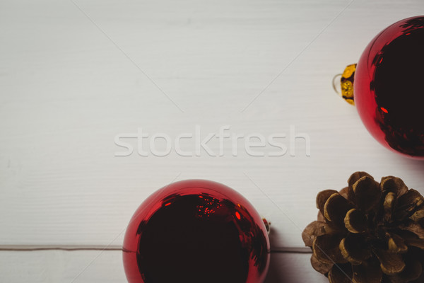 Red christmas bauble and pine cone on wooden table Stock photo © wavebreak_media