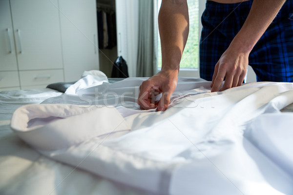 Man unbuttoning his white shirt in bedroom Stock photo © wavebreak_media