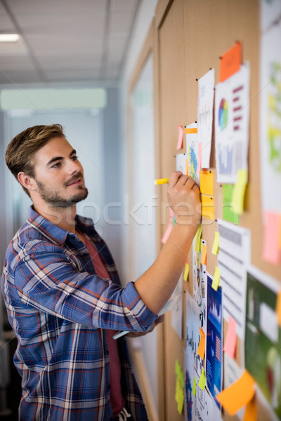 Man writing on the sticky note on the board Stock photo © wavebreak_media