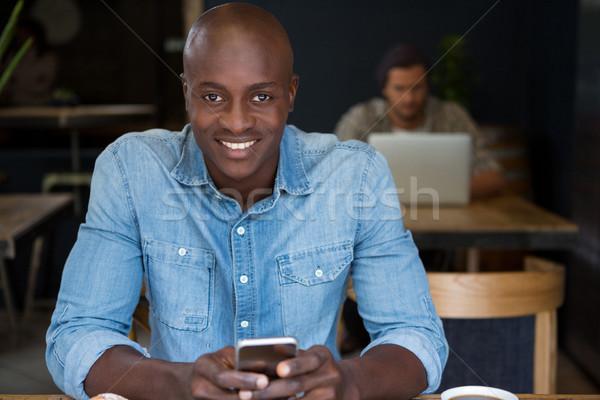 Happy man using digital tablet in coffee house Stock photo © wavebreak_media