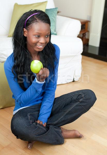 Jolly woman eating an apple sitting on the floor Stock photo © wavebreak_media