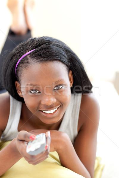 Happy young woman watching TV lying on a sofa Stock photo © wavebreak_media