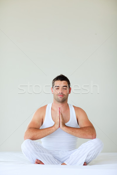 Young man doing yoga in bed with clossed eyes Stock photo © wavebreak_media