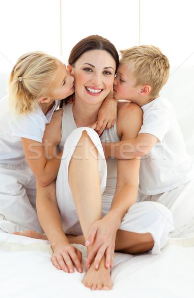 Adorável irmãos beijando mãe sessão cama Foto stock © wavebreak_media