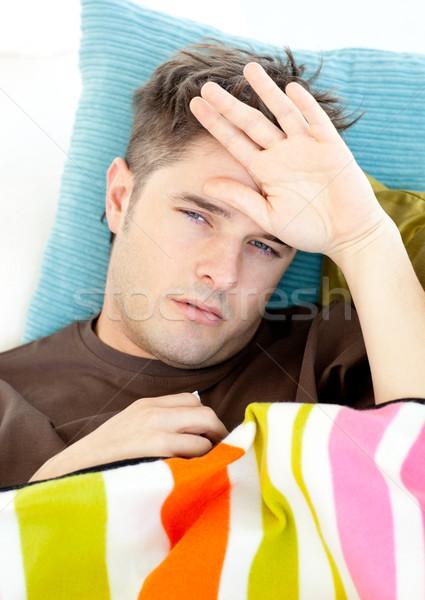 Malade jeune homme sensation température canapé salon Photo stock © wavebreak_media