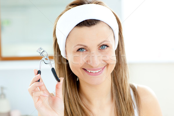 Smiling woman holding an eylash curler looking at the camera in the bathroom Stock photo © wavebreak_media