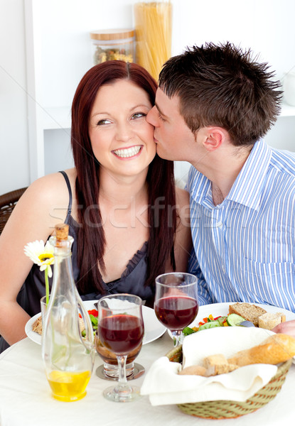 Handsome boyfriend giving a kiss to his attractive girlfriend during dinner at home Stock photo © wavebreak_media