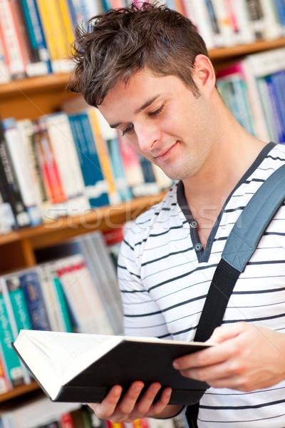 Cute male student reading a book in a bookstore Stock photo © wavebreak_media