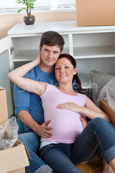 Stock photo: happy couple in their new home sitting on the floor among cardboard boxes in their new kitchen