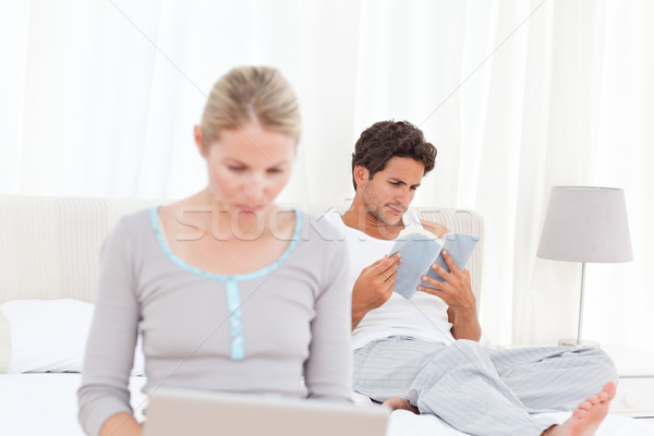 Woman working on her laptop while her husband is reading Stock photo © wavebreak_media