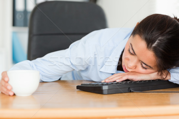 Frontal view of a good looking woman sleeping on a keyboard while holding a cup of coffee at the off Stock photo © wavebreak_media