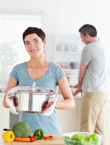 Charming wife holding a pot while her husband is washing the dishes in a kitchen Stock photo © wavebreak_media