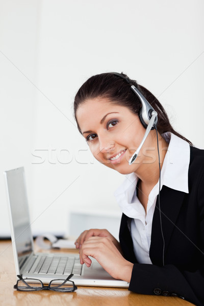 A smiling young operator with a headset is helping someone via headset in her office Stock photo © wavebreak_media