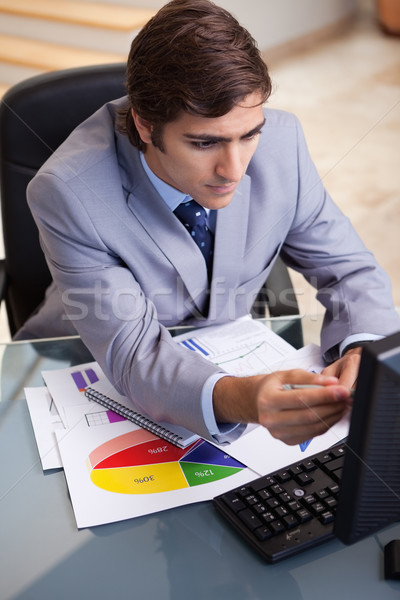 Young businessman analyzing statistics Stock photo © wavebreak_media