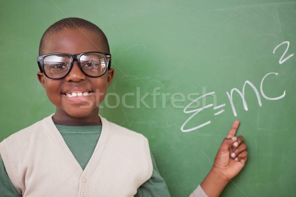 Smart schoolboy showing the the mass-energy equivalence formula on a blackboard Stock photo © wavebreak_media