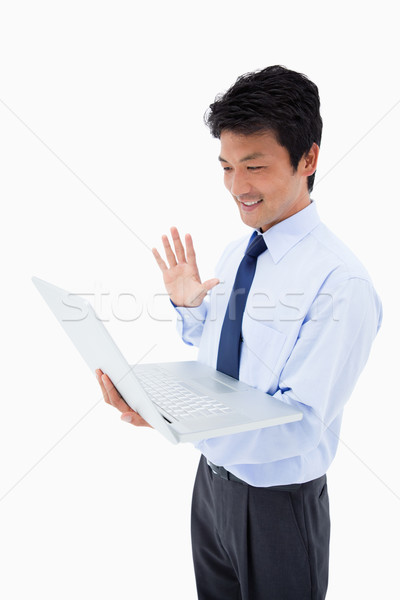 Portrait of a businessman waving at a laptop against a white background Stock photo © wavebreak_media