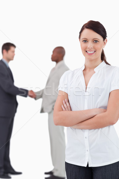 Tradeswoman with arms folded and hand shaking trading partners behind her against a white background Stock photo © wavebreak_media