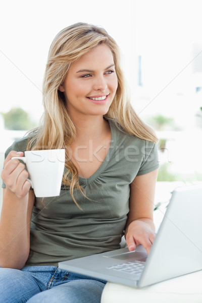 A woman looking slightly sideways, as she uses her laptop and holds a cup, while sitting on the couc Stock photo © wavebreak_media