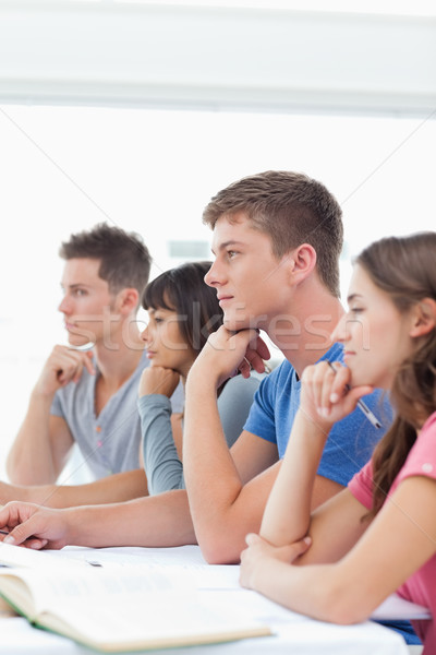 A class of students sitting beside one another and listening  Stock photo © wavebreak_media