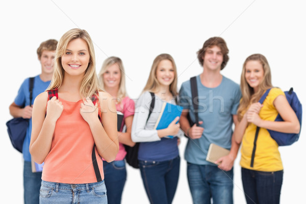 A smiling girl stands in front of her college friends as they all look at the camera  Stock photo © wavebreak_media