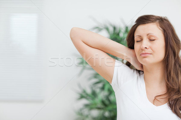 Woman placing her hand on her painful neck in a room Stock photo © wavebreak_media