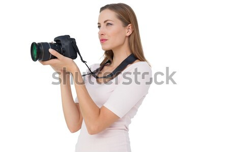 Woman smiling while holding a SLR camera against white background Stock photo © wavebreak_media