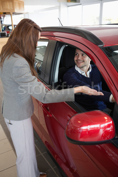 Stock photo: Businesswoman presenting the car to a client in a dealership