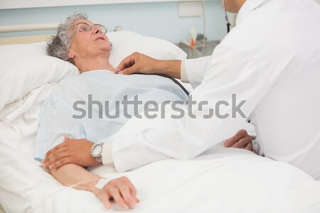 Elderly female patient smiling up at nurse and doctor from hospital bed Stock photo © wavebreak_media