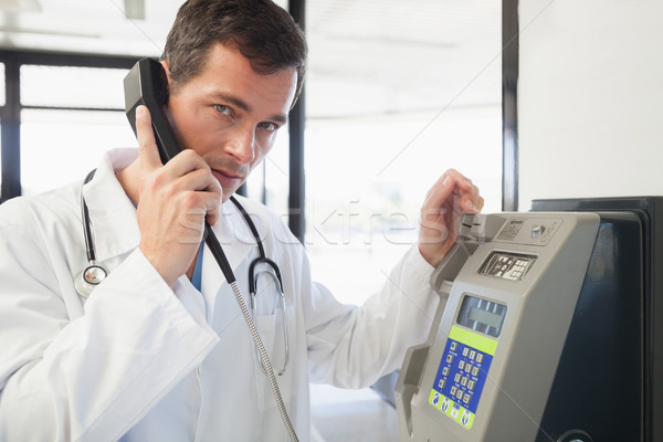 Doctor phoning in the hospital corridor Stock photo © wavebreak_media