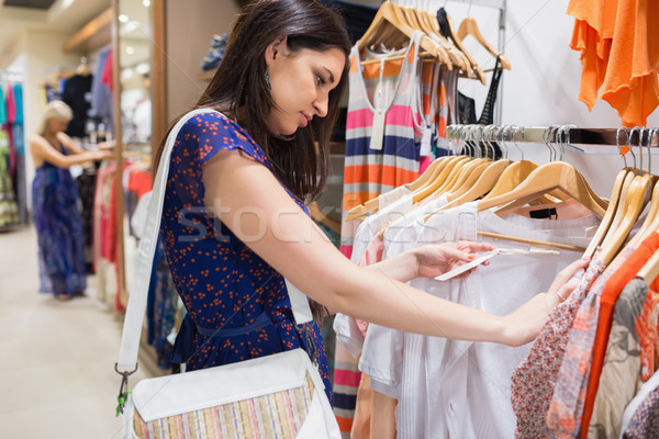 Woman with bag looking through clothes in shopping mall Stock photo © wavebreak_media