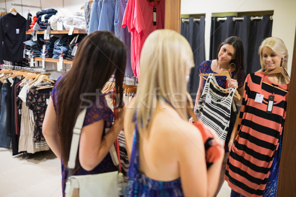 Two women smiling in front of the mirror in clothing store Stock photo © wavebreak_media