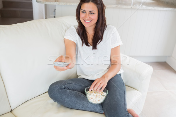 Woman smiling and changing channel on sofa Stock photo © wavebreak_media