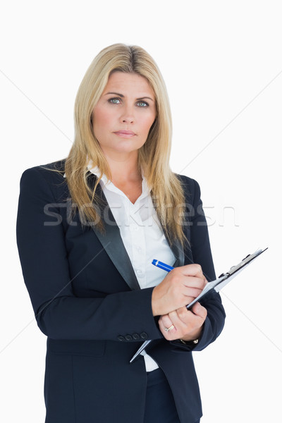 Serious business woman writing in the clipboard in the white background Stock photo © wavebreak_media
