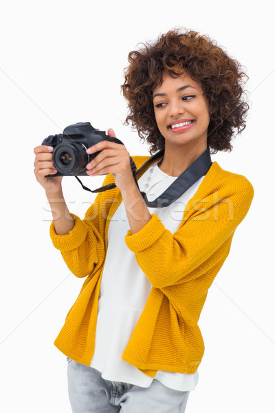 Smiling girl holding digital camera and looking at it Stock photo © wavebreak_media