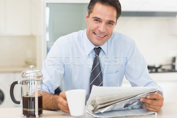 Smiling well dressed man with coffee cup and newspaper in kitche Stock photo © wavebreak_media