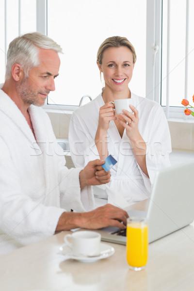 Smiling couple using laptop at breakfast in bathrobes Stock photo © wavebreak_media