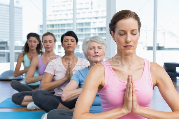 Class sitting with joined hands in row at yoga class Stock photo © wavebreak_media