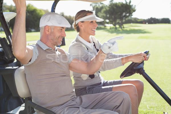 Happy golfing couple smiling in their buggy Stock photo © wavebreak_media